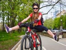 Велосипед задействуя шлем девушки нося с ногами врозь Стоковое фото RF