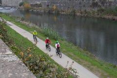 3 велосипедиста ехать вдоль обваловки реки Bisenzio Prato Тоскана Италия Стоковое Изображение