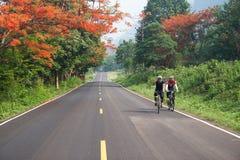 2 велосипедиста ехать на красивой дороге в Kanchanaburi, Таиланд, Стоковое фото RF