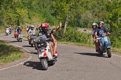 Велосипедисты ехать винтажный Vespa самоката Стоковые Изображения