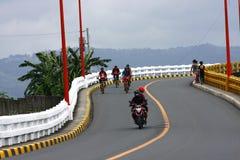 Велосипедисты и всадники мотоцикла пересекают мост Tumana в городе Marikina стоковое изображение