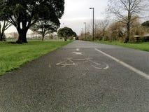 Велосипедисты и пешеход покрасили знак на тропе Стоковое Изображение