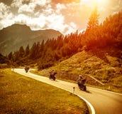 Велосипедисты на дороге гор в заходе солнца Стоковые Фотографии RF