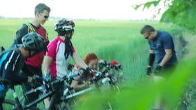 Велосипедисты нося велосипеды через высокую траву видеоматериал