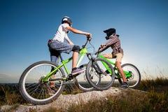 Велосипедисты с горными велосипедами на холме под голубым небом Стоковое фото RF