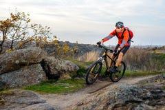 Велосипедист в красной куртке ехать велосипед на скалистом следе весьма спорт стоковая фотография rf
