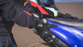 Велосипедист в улице рядом с его велосипедом, кладет дальше перчатки акции видеоматериалы