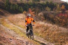 Велосипедист в sportive оранжевой куртке ехать горный велосипед вдоль следа в сельской местности на заходе солнца Стоковое фото RF