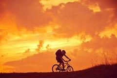 Велосипедист горы в восходе солнца Стоковые Изображения