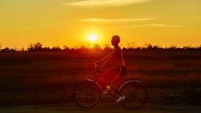 Велосипедист-девушка на заходе солнца Стоковые Изображения RF