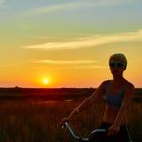 Велосипедист-девушка на заходе солнца Стоковые Изображения