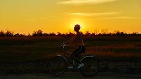 Велосипедист-девушка на заходе солнца Стоковое Изображение