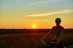 Велосипедист-девушка на заходе солнца Стоковые Фотографии RF