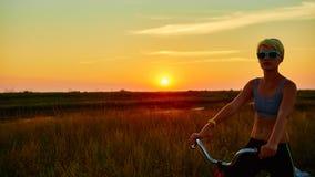 Велосипедист-девушка на заходе солнца Стоковое фото RF