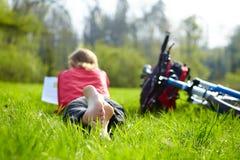 Велосипедист девушки на остановке читает на зеленой траве outdoors весной паркует Стоковая Фотография