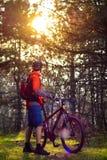 Велосипедист ехать велосипед на следе в красивой Fairy концепции приключения и перемещения соснового леса Стоковые Изображения RF