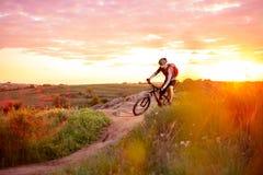 Велосипедист ехать велосипед на следе горы скалистом на заходе солнца Стоковое Изображение RF