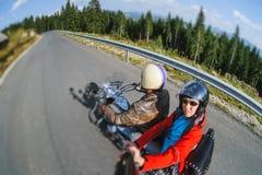 Велосипедист ехать его мотоцикл на дороге с пассажиром Стоковая Фотография