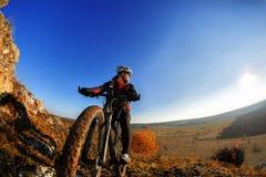 Велосипедист ехать холм велосипеда вниз скалистый на заходе солнца Закройте вверх по весьма концепции спорта Космос для текста Стоковые Изображения RF