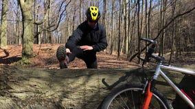 Велосипедист делая его подогрев на следе природы, стоя около велосипеда видеоматериал