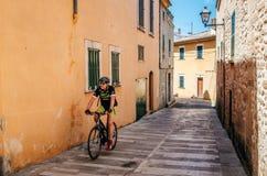 Велосипедист едет вдоль узкой улицы старого Alcudia, Мальорки стоковые изображения