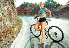 Велосипедист женщины стоя около велосипеда на дороге горы Стоковые Изображения