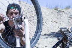 Велосипедист исправляя колесо велосипеда BMX Стоковые Фотографии RF