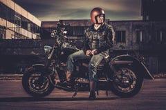 Велосипедист и его мотоцикл стиля bobber стоковое фото rf