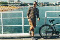 Велосипедист молодого человека стоит на пристани и наслаждается видом на море Концепция деятельности при перемещения праздника Стоковое Изображение RF