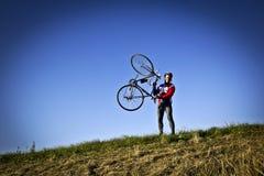Велосипедист на поле рядом с положением велосипеда, удерживание его велосипед в руках Стоковые Изображения