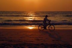 Велосипедист на пляже на заходе солнца Стоковые Фото