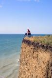 Велосипедист на скале над морем Стоковые Фото