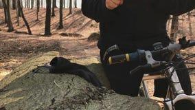 Велосипедист останавливает для того чтобы проверить его smartwatch стоя в листьях покрыл forrest видеоматериал