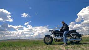 Велосипедист, остатки мотоциклиста на его мотоцикле в зеленом поле под облаками 4K акции видеоматериалы
