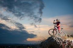 Велосипедист по пересеченной местностей ослабляя на верхней части горы Стоковые Изображения