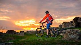 Велосипедист при его горный велосипед смотря красивый заход солнца на следе весны скалистом Весьма спорт и концепция приключения Стоковые Изображения RF