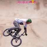 Велосипедист скачет перед красным логотипом Bull Стоковые Изображения