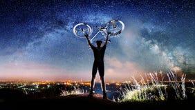 Велосипедист с велосипедом в ноче под звёздным небом Стоковое фото RF