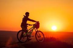 Велосипедист с горным велосипедом на холме в вечере Стоковые Изображения RF