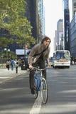 Велосипед катания бизнесмена на городской улице Стоковое Изображение RF