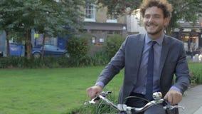 Велосипед катания бизнесмена через парк города видеоматериал
