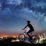 Велосипед катания велосипедиста в ноче под звёздным небом Стоковая Фотография
