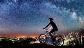 Велосипед катания велосипедиста в ноче под звёздным небом Стоковые Изображения RF