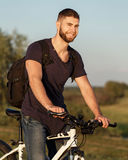 Велосипед катания велосипедиста молодого человека в древесине на заходе солнца Стоковое фото RF