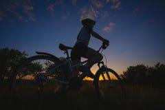 велосипед катания велосипедиста на заходе солнца Стоковые Фотографии RF