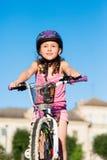 Велосипед катания девушки ребенка на заходе солнца лета в парке Стоковая Фотография
