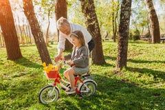 Велосипед катания девушки человека уча Стоковое фото RF