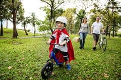 Велосипед катания мальчика супергероя с семьей в парке Стоковые Фотографии RF