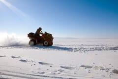 Велосипед квада катания человека на снежном поле зимы Стоковое Фото