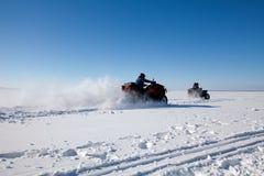 Велосипед квада катания человека на снежном поле зимы Стоковые Фото